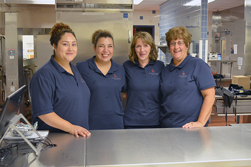 Four women standing in school kitchen
