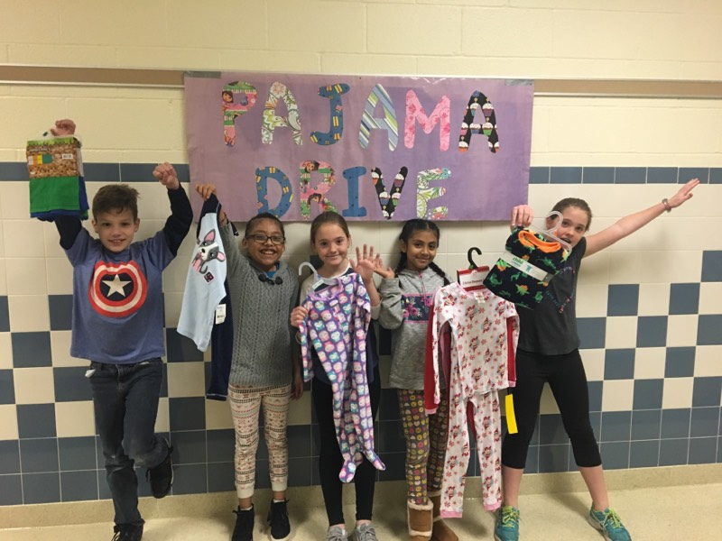 Students holding donations of pajamas