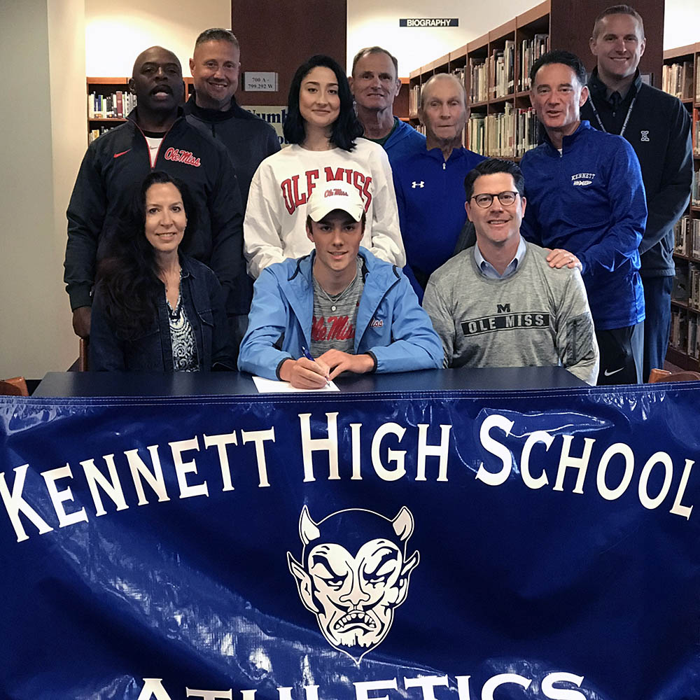 student-athlete surrounded by coaches and family